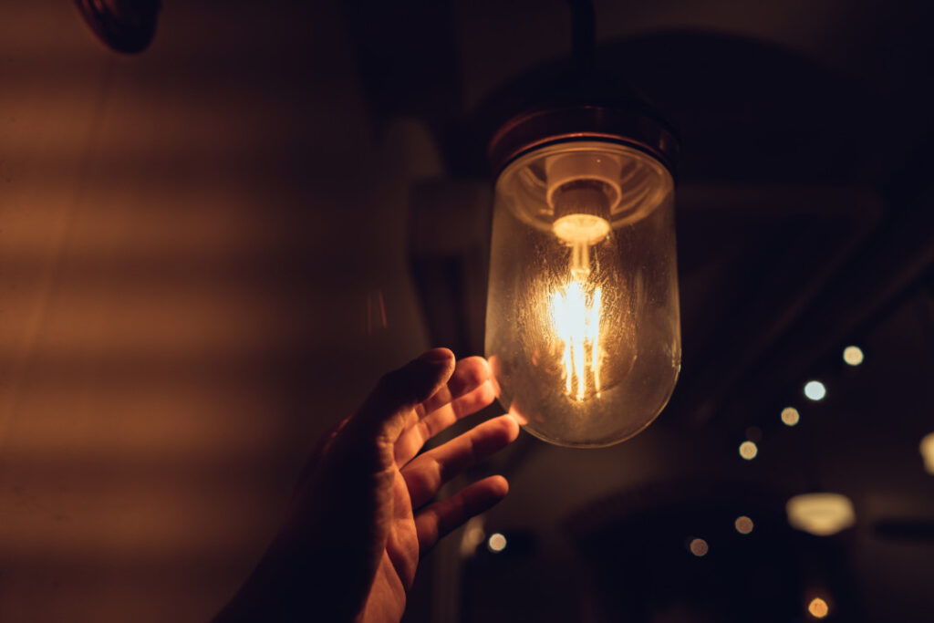 Hand berührt Glühbirne